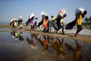 Rohingya refugee workers carry bags of salt as they work in processing yard in Cox's Bazar, Bangladesh, 12 April 2017. (Photo: Reuters/Mohammad Ponir Hossain).