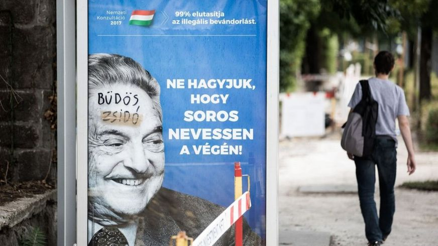 A poster showing George Soros, on which someone has written