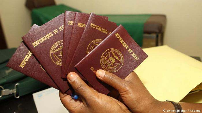Two hands holding several Malian passports (picture alliance / Godong)